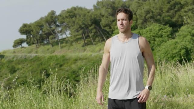 man jumping while warming up before jogging - rozgrzewka filmów i materiałów b-roll