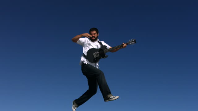 Man jumps into sky playing electric guitar, slow motion video