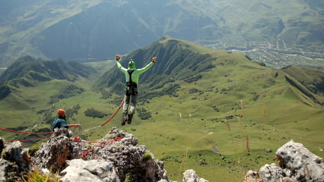 a man jumps off the top of the mountain. - bungee jumping video stock e b–roll