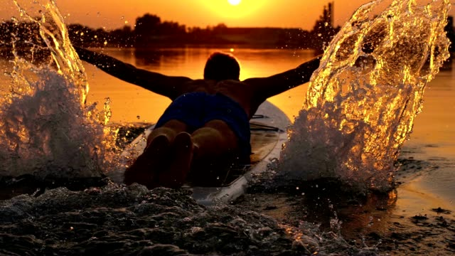 vídeos y material grabado en eventos de stock de en cámara lenta hombre salta en la tabla de surf - embarcación marina