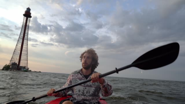 Man kayaking to  lighthouse at sunset