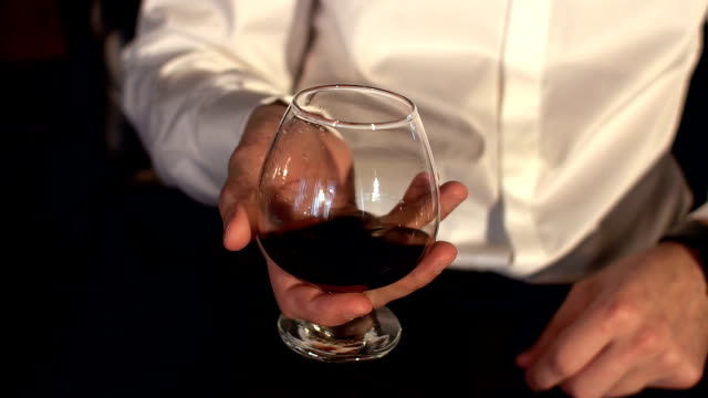Man keeping a glass of cognac, close-up. Slow mo. video