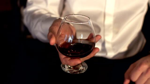 man keeping a glass of cognac, close-up. - brandy video stock e b–roll