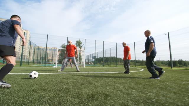 stockvideo's en b-roll-footage met mens die schoppen de bal richting netto - samen sporten