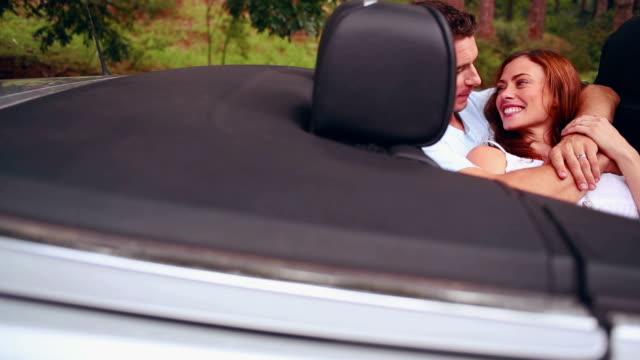 Man kissing his girlfriend in a convertible car