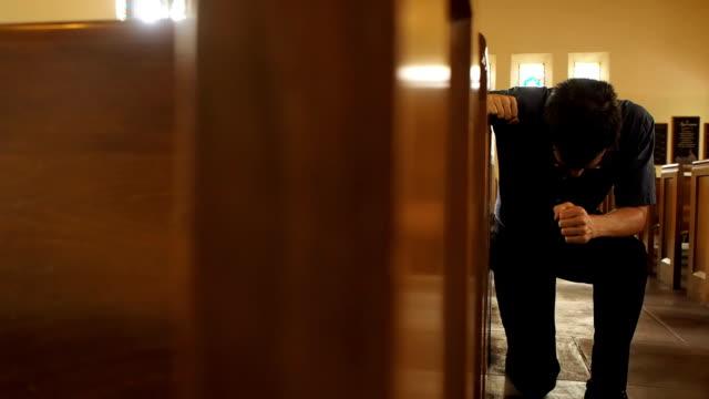 stockvideo's en b-roll-footage met man kneeling in prayer - kerk