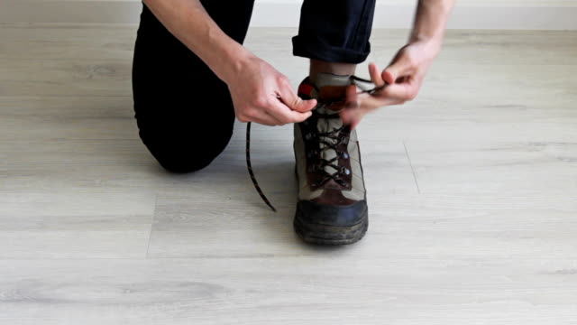 Man Lacing Up Dirty Boots .