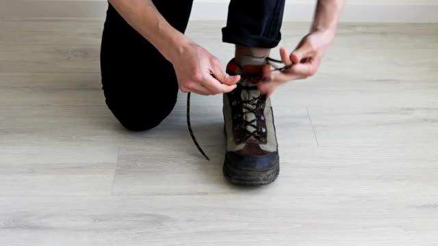 mann schnüren bis schmutzige stiefel. - menschlicher finger stock-videos und b-roll-filmmaterial