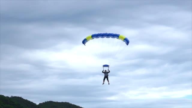 vídeos de stock, filmes e b-roll de homem pousar seu para-quedas na praia - paraquedismo