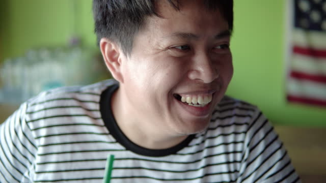 Man laughing with friends in local coffee shop.