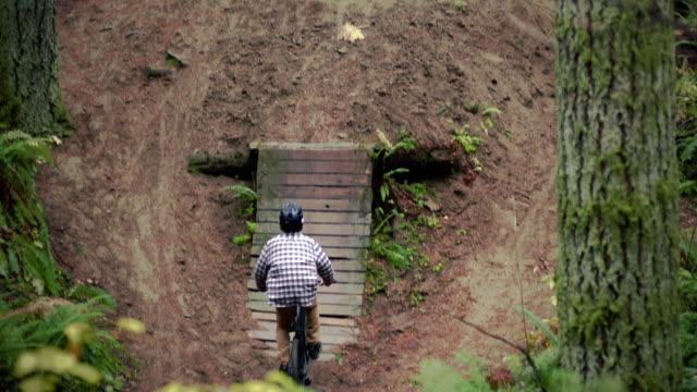 森の中でダートバイクジャンプに大きな空気を打ち上げる男 ビデオ