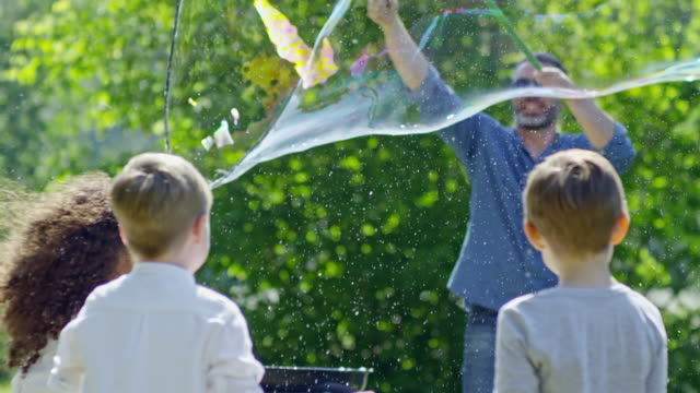 Man Launching Giant Bubble Up in the Air at Kids Party Tilt up of man making giant soap bubble for little kids in park. Boys and girl trying to catch bubble while it flying up in the air giant fictional character stock videos & royalty-free footage