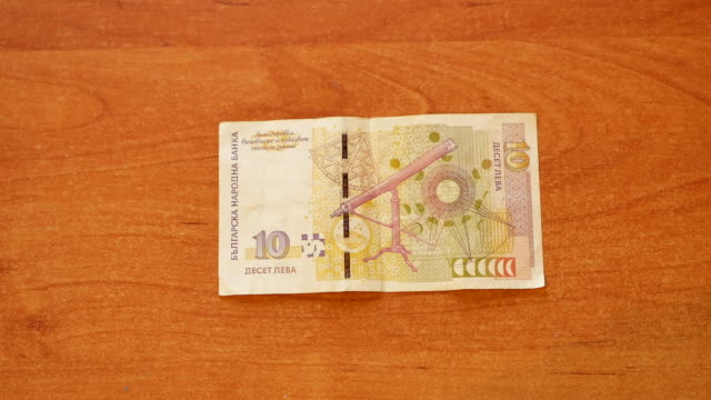 man lay Bulgarian lev money and Euro on top man put Bulgarian lev banknote on wooden desk and put 50 Euros on top and clap his hand on pile as a symbol of Bulgaria and European Union integration. close-up 4k video footage POV schengen agreement stock videos & royalty-free footage
