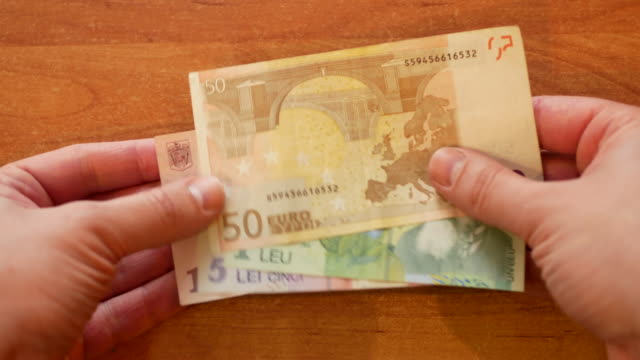 man lay out Romanian LEI and Euro on desk man lay out spread out Romanian LEI on wooden desk and put 50 Euros on top and clap his hand on pile as a symbol of Romania and European Union integration. close-up 4k video footage POV schengen agreement stock videos & royalty-free footage