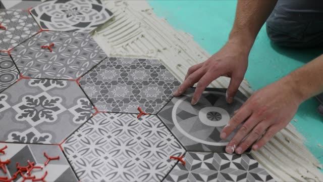 man laying hexagon floor tiles - мозаика стоковые видео и кадры b-roll