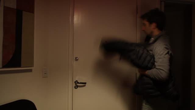 L'homme quitte la maison, ouvre la porte d'entrée, ferme la porte et se transforme en lumière éteinte. - Vidéo