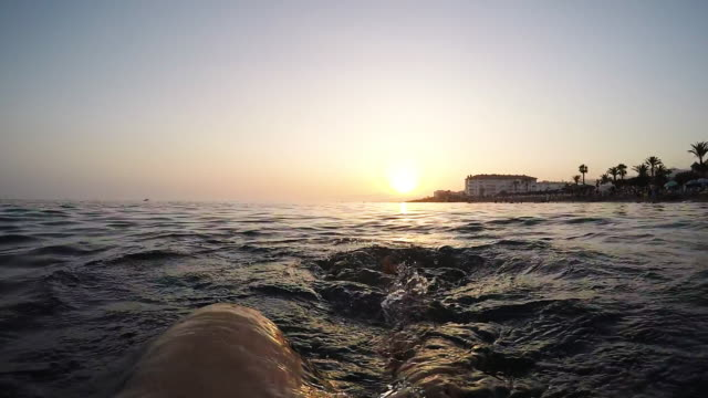 Man legs swimming to back in a calm beach at sunset - First person view