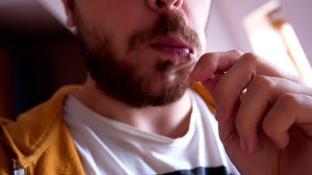 man licking lollipop - lecca lecca video stock e b–roll