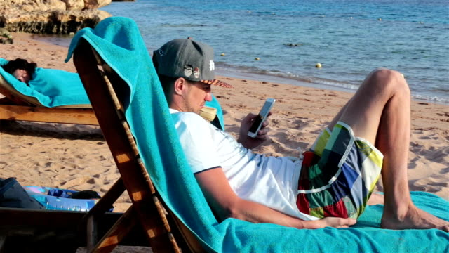 Man lies on a deckchair and using a smartphone for work. Rest on the sea. The man lies on a deckchair in the evening. He uses a mobile phone for work. Sharm El Sheikh. Egypt. lounge chair stock videos & royalty-free footage