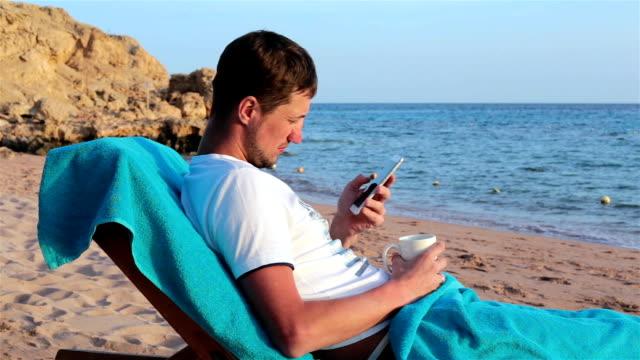 man liegt auf einem liegestuhl und nutzt ein smartphone zur arbeit. - sun chair stock-videos und b-roll-filmmaterial