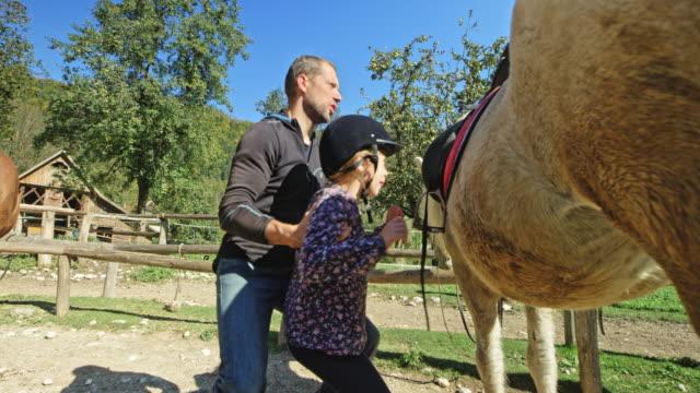 日差しの中で馬にサドルに子供を持ち上げる男 - スポーツ用品点の映像素材/bロール