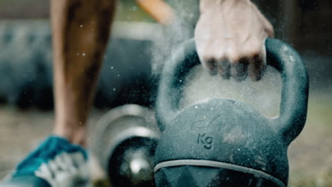 SUPER SLO MO Man lifting a heavy kettlebell Super slow motion shot of an unrecognizable man lifting kettlebell full of sport chalk from a lawn on the backyard. strength stock videos & royalty-free footage
