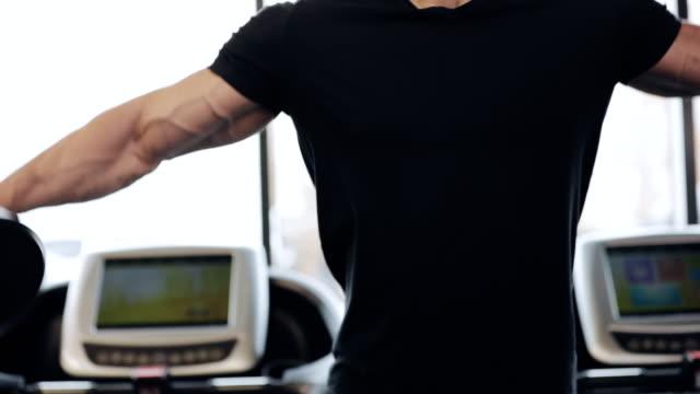 vídeos de stock, filmes e b-roll de homem levanta um haltere no ginásio, ele músculos deltoide de bombeamento - comodidades para lazer