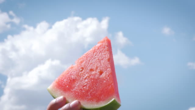 A Man Lifts a Watermelon Slice into the Summer Sky A man lifts a slice of watermelon high into the summer sky. The bright red and green contrasts with the blue sky and puffy white clouds. The fresh fruit stands for freedom of summer vacations, raw food and family picnics. watermelon stock videos & royalty-free footage