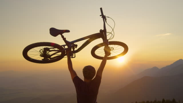 CLOSE UP Man lifts his bicycle above head at sunset after a mountain biking trip