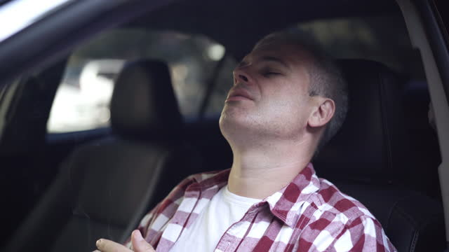 Man lightning cigarette and smoking sitting in car on driver's seat. Close-up portrait of stressed Caucasian middle aged guy smokes inside automobile. Bad habits and unhealthy lifestyle