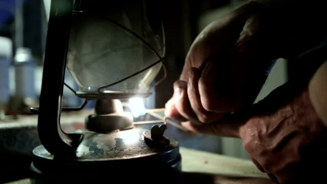 man lights a oil lamp at night - lanterna attrezzatura per illuminazione video stock e b–roll