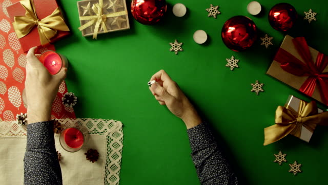 Man lights Christmas candles on table with chroma key, top down shot video