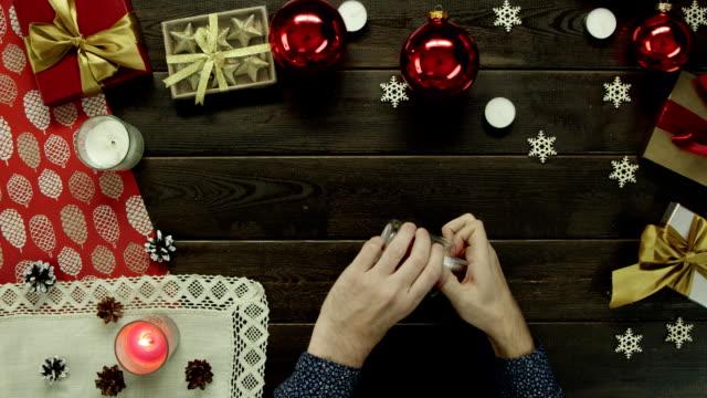 男は装飾休日デスク、ショットをトップダウンでクリスマス キャンドルを点灯します。 ビデオ