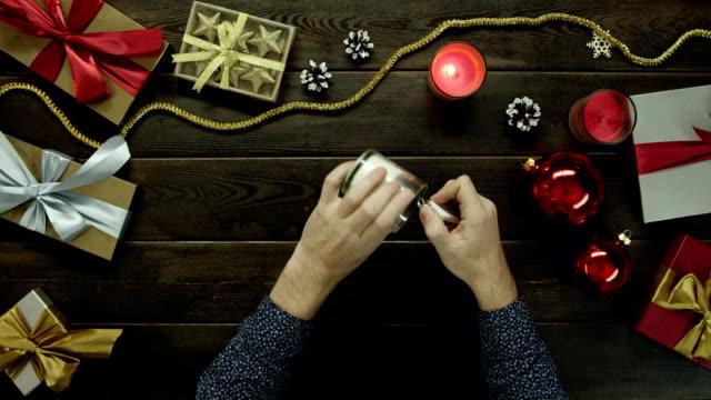 男は、ショット トップダウンの休日テーブルのクリスマスのキャンドルが点灯します。 ビデオ