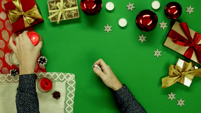 Man lights Xmas candles on table with chroma key, top down shot video