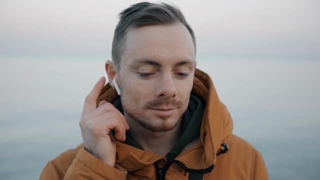 Man listening his playlist touching wireless earphones at the sea beach video