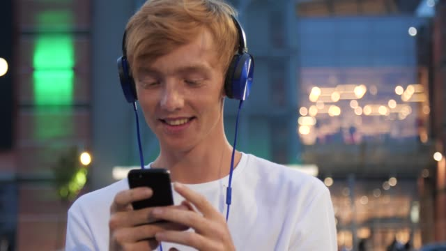 Man Listening Music In Headphones With Phone Near Shopping Mall Man Listening Music In Headphones With Phone Near Shopping Mall, Redhead Guy Using Smartphone On Street redhead stock videos & royalty-free footage
