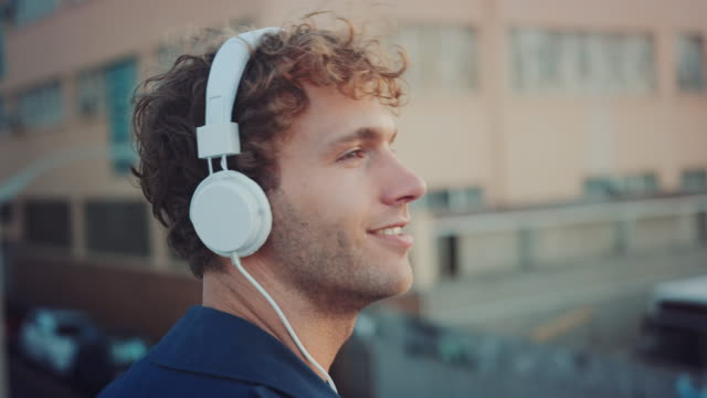 Man listening to music on rooftop A man standing on a rooftop. He listens to music from his smartphone with headphones. headphones stock videos & royalty-free footage
