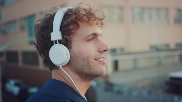vidéos et rushes de un homme écouter de la musique sur le toit - casque audio