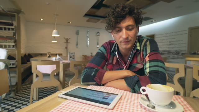 Man listening to music with headphones and digital tablet. video