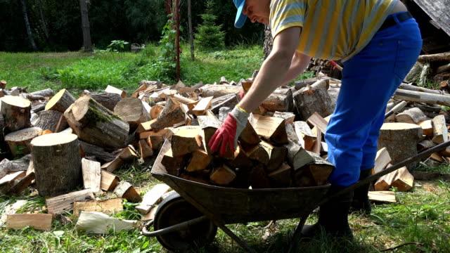 mann lade brennholz in schubkarre in dorf im sommer. 4k - brennholz stock-videos und b-roll-filmmaterial