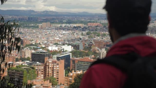 Hombre mirando a Bogotá desde la montaña - vídeo