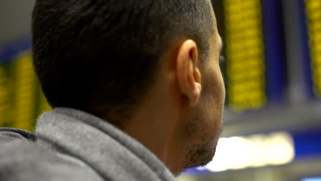 человек, глядя на электронный стол в аэропорту, поиск информации о времени регистрации - табло вылетов и прилётов стоковые видео и кадры b-roll