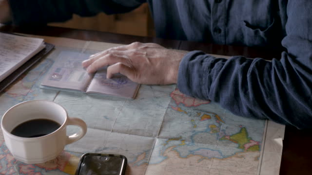 man looking at his passport stamps and a world map while writing in notebook - passports and visas stock videos and b-roll footage
