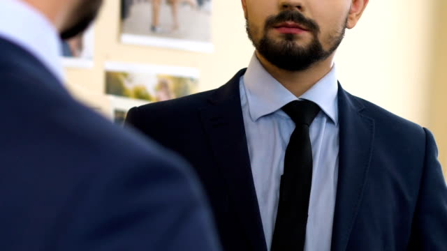 Man looking at mirror reflection trying on business suit, first day at new work video