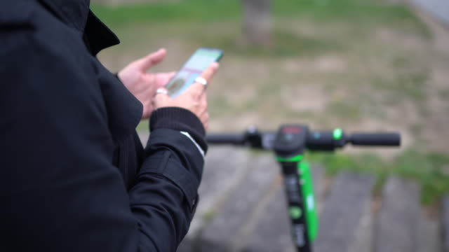 man looking at navigation map on his mobile phone - monopattino elettrico video stock e b–roll