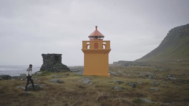 Man looking at scenic view of lighthouse in Iceland