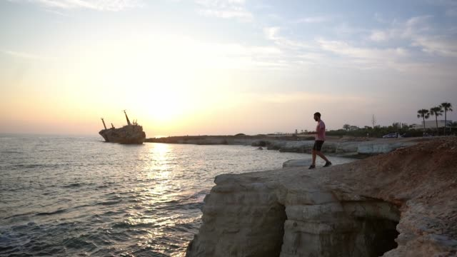 Man looking at scenic view of seaside and ship wreck of Cyprus