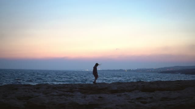 Man looking at scenic view of seaside at sunset