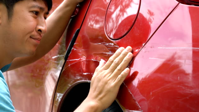 vidéos et rushes de homme regardant des rayures sur sa voiture. - endommagé